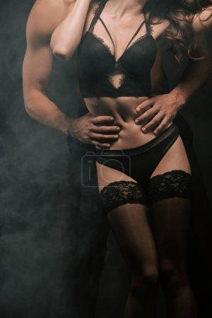 Ausgeschnittene Ansicht eines leidenschaftlichen Mannes, der junge Frau in Unterwäsche auf schwarz mit Rauch umarmt