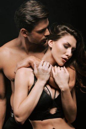 Photo pour Un homme passionné serrant une jeune femme en sous-vêtements isolée sur un noir - image libre de droit