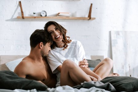 Photo for Muscular man smiling near happy girlfriend in bedroom - Royalty Free Image