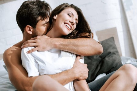Photo for Selective focus of muscular boyfriend embracing cheerful girlfriend in bedroom - Royalty Free Image