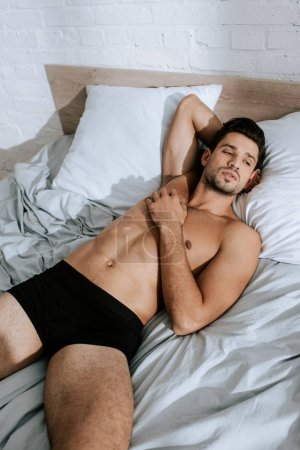 Photo pour La lumière du soleil sur un homme sans chemise reposant sur son lit à la maison - image libre de droit