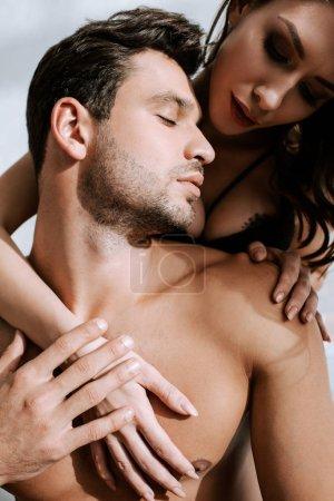Photo pour Jeune belle femme étreignant homme torse nu à la maison - image libre de droit