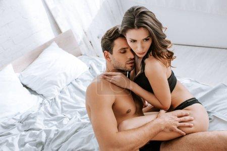 Photo pour Vue aérienne d'une fille sexy en lingerie noire serrant un homme dans sa chambre - image libre de droit