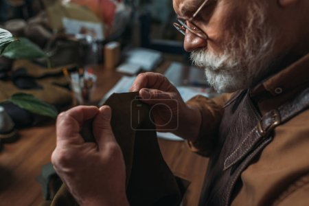 Photo pour Attention, cordonnier senior tenant un morceau de cuir authentique en atelier - image libre de droit