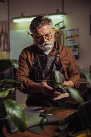 Photo for Bearded senior shoemaker holding detail of unfinished shoe in workshop - Royalty Free Image