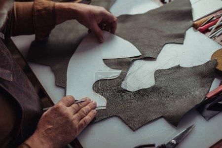 Photo pour Vue recadrée du cordonnier tenant un morceau de cuir près du gabarit dans l'atelier - image libre de droit