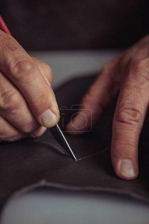 Photo pour Vue recadrée du cordonnier découpe cuir véritable avec couteau - image libre de droit