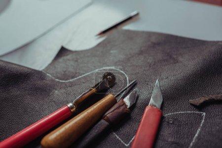 Photo pour Mise au point sélective de différentes fraises et de la roue traceuse sur un morceau de cuir véritable en atelier - image libre de droit