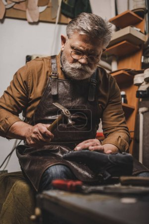 Photo for Senior, bearded shoemaker holding shoe while repairing shoe in workshop - Royalty Free Image