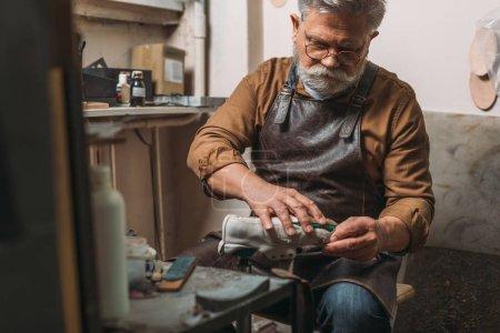 Photo pour Foyer sélectif de senior, cordonnier barbu réparation de chaussures dans l'atelier - image libre de droit