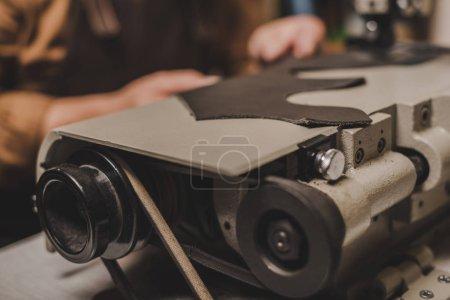 Photo pour Mise au point sélective d'une pièce de cuir authentique sur une machine à coudre près du cordonnier en atelier - image libre de droit