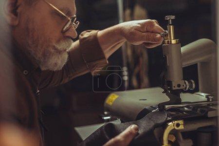 Photo pour Focalisation sélective du cordonnier senior couture cuir authentique sur machine à coudre en atelier - image libre de droit