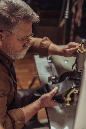 Photo pour Focalisation sélective du cuir à coudre du cordonnier senior sur la machine à coudre en atelier - image libre de droit