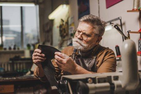 Photo pour Cordonnier âgé et attentif tenant un morceau de cuir authentique près d'une machine à coudre - image libre de droit