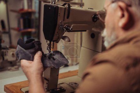Photo for Selective focus of cobbler sewing part of suede shoe on sewing machine - Royalty Free Image