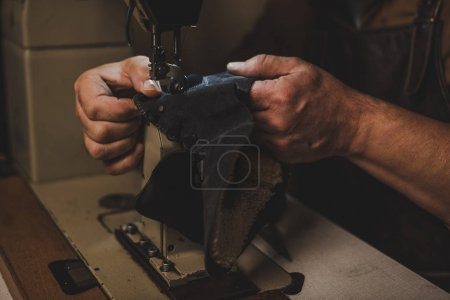 Photo for Cropped view of cobbler sewing part of leather shoe on sewing machine - Royalty Free Image