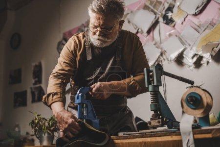 Photo pour Cordonnier principal faisant des trous dans le cuir avec poinçon - image libre de droit