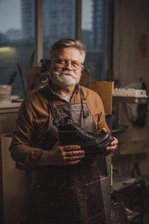 Photo pour Positif, cordonnier chevronné souriant à la caméra en tenant une botte en cuir - image libre de droit
