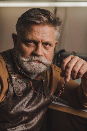 Photo pour Senior, confident cobbler looking at camera while holding glasses - image libre de droit