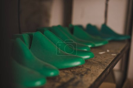 Photo for Selective focus of different shoe lasts on rack in workshop - Royalty Free Image