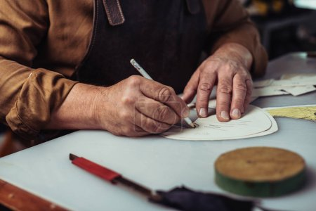 Photo for Cropped view of shoemaker making template in workshop - Royalty Free Image