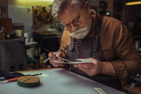 Photo pour Cordonnier à la mode regardant un gabarit en papier dans un atelier - image libre de droit