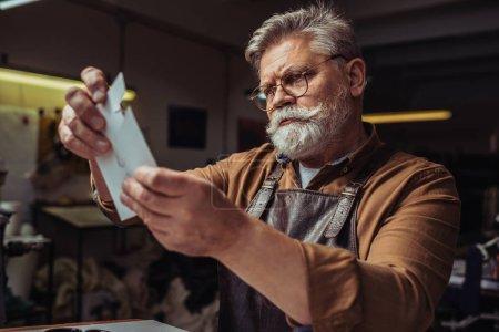 Photo pour Un cordonnier âgé et attentif regardant un modèle en atelier - image libre de droit