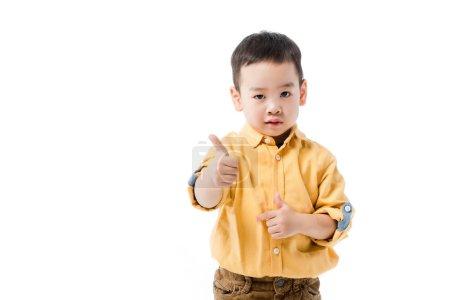 Photo pour Grave asiatique garçon montrant pouce jusqu 'isolé sur blanc - image libre de droit