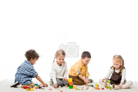 multicultural children playing with wooden blocks on carpet, isolated on white