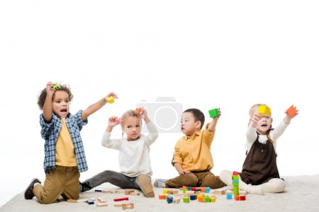 emotional multicultural children playing with wooden blocks on carpet, isolated on white