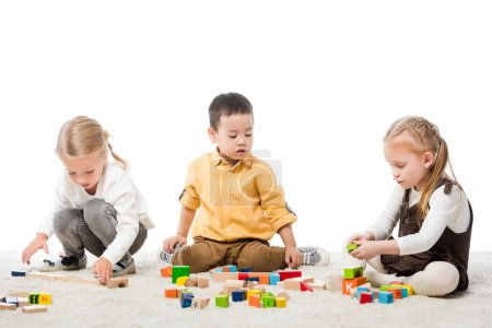 multiethnic kids playing with wooden blocks on carpet, isolated on white