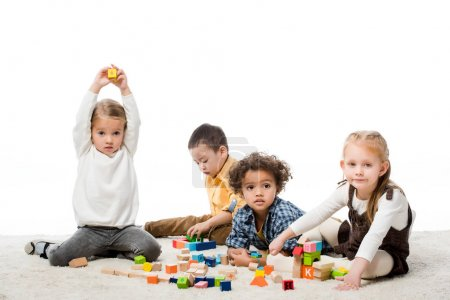 adorable multiethnic kids playing with wooden blocks on carpet, isolated on white