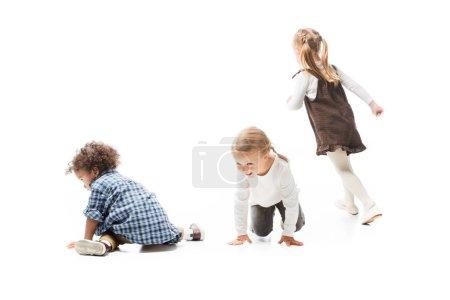 Foto de Divertidos niños multiculturales jugando juntos, aislados en blanco - Imagen libre de derechos