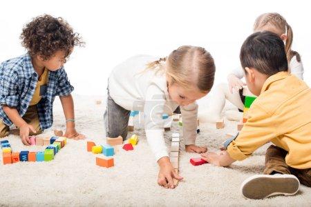 Foto de Niños multiétnicos jugando con bloques de madera en la alfombra, aislados en blanco. - Imagen libre de derechos