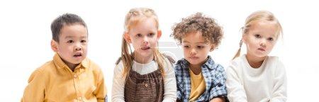 Foto de Foto panorámica de niños multiculturales lindos que se sientan aislados en blanco - Imagen libre de derechos