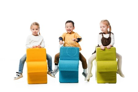 Photo for Multiethnic kids sitting on puzzle chairs, isolated on white - Royalty Free Image