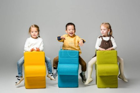 Photo for Happy multicultural kids sitting on puzzle chairs, on grey - Royalty Free Image
