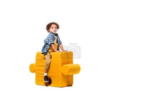 Photo pour Afro-américain garçon assis sur chaise puzzle jaune, isolé sur blanc - image libre de droit