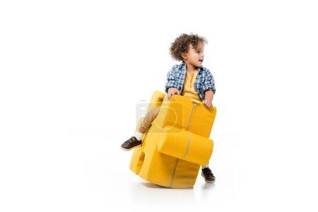 Photo pour Heureux garçon afro-américain assis sur chaise puzzle jaune, isolé sur blanc - image libre de droit