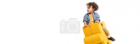 Photo for Panoramic shot of little african american boy sitting on yellow puzzle chair, isolated on white - Royalty Free Image