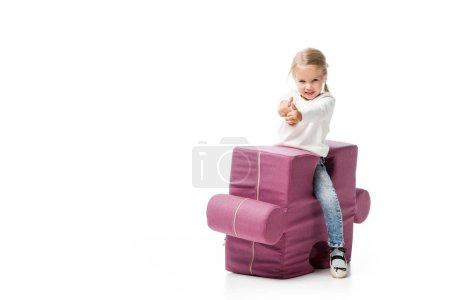 Foto de Jovencito feliz mostrando pulgares en silla de rompecabezas púrpura, aislado en blanco. - Imagen libre de derechos