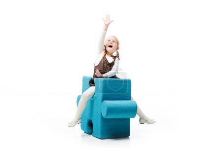 aufgeregtes Kind auf blauem Puzzlestuhl sitzend, isoliert auf weißem