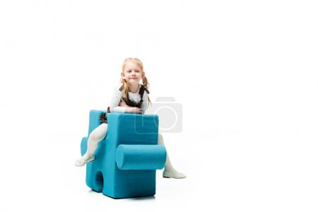Photo for Cheerful kid sitting on blue puzzle chair, isolated on white - Royalty Free Image