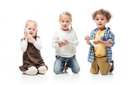 Photo pour Enfants multiethniques parler smartphones tout en étant assis sur blanc - image libre de droit