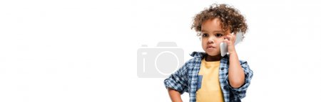 Photo for Panoramic shot of serious african american boy talking on smartphone, isolated on white - Royalty Free Image