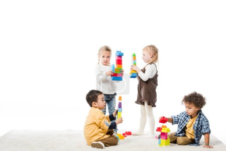 multiethnic children playing with wooden blocks on carpet, isolated on white