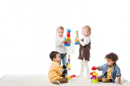 Foto de Niños multiétnicos jugando con bloques de madera en la alfombra, aislados en blanco - Imagen libre de derechos
