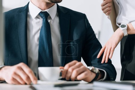 cropped view of secretary touching hand of businessman in office