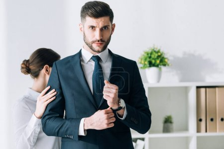 Photo for Secretary touching hand of confident and handsome businessman in office - Royalty Free Image