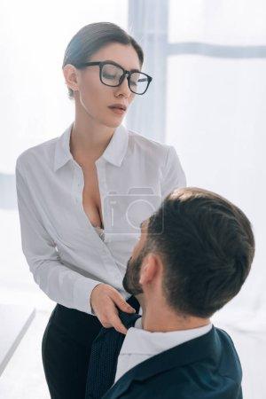 Photo pour Sexy secrétaire avec gros seins tirant la cravate de l'homme d'affaires en fonction - image libre de droit
